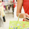 Close-up of womans hand holding plastic card while going shopping in the mall